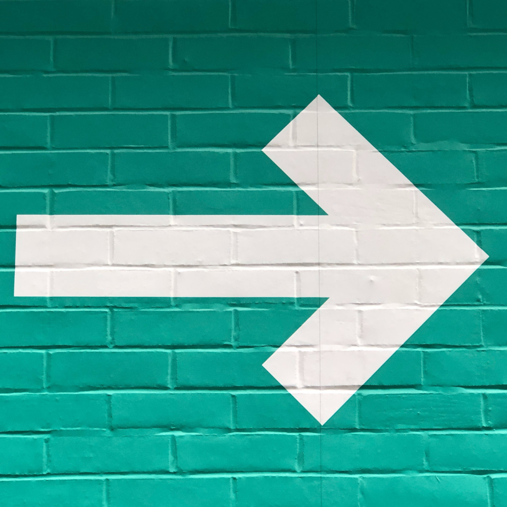 White arrow over green wall